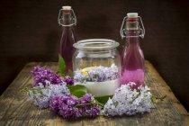 Garrafas de vidro de sirup lilás caseiro e ingredientes em vidro — Fotografia de Stock