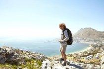 Южная Африка, Кейптаун, улыбающийся молодой человек, стоящий на побережье и смотрящий на вид — стоковое фото