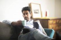 Портрет задумчивого человека с кофейной кружкой и планшетом, сидящего дома на диване — стоковое фото