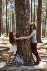Щаслива молода пара обіймає дерево в лісі — стокове фото