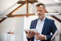 Uomo d'affari maturo utilizzando tablet in ufficio — Foto stock