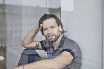 Ritratto di bell'uomo caucasico seduto alla finestra nella stanza e che guarda la macchina fotografica — Foto stock