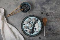Bol à smoothie bleu avec noix de coco râpée, myrtilles et boules de fruits du dragon — Photo de stock