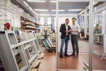 Два бізнесмени в заводі дивлячись на планшеті — стокове фото