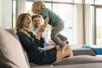 Счастливые родители играют с сыном на диване дома — стоковое фото