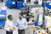 Geschäftsleute nutzen Tablet bei Besprechung in Produktionshalle — Stockfoto