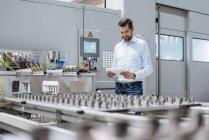 Homme d'affaires à la machine dans l'usine regardant la tablette — Photo de stock