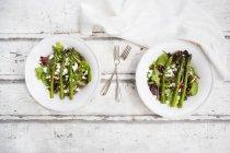 Смешанный салат с жареной зеленой спаржей, семенами феты и граната — стоковое фото