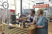 Salesperson helping customer in bicycle shop — Stock Photo