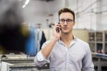 Young businessman on cell phone in factory — Stock Photo