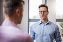 Dois homens de negócios a falar à janela — Fotografia de Stock