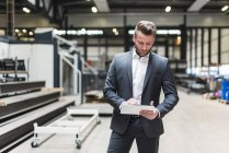 Бізнесмен з планшетом стоячи на підлозі заводу магазин — стокове фото