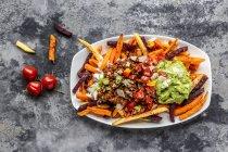 Овощной картофель фри с вегетарианским болоньезе, гуакамоле, йогуртовым соусом, помидорами, весенним луком и пармезаном на тарелке — стоковое фото