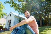 Портрет бородатого мужчины, сидящего перед домом — стоковое фото