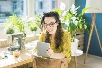 Portrait of smiling fashion designer sitting in her studio using tablet — Stock Photo