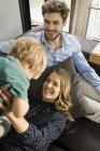 Padres felices jugando con su hijo en el sofá en casa - foto de stock