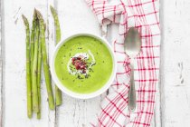 Green asparagus soup with pomegranate seeds and black sesame — Photo de stock