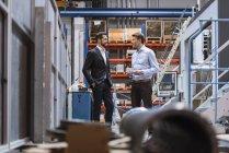 Двоє бізнесменів обговорюють в заводських умовах — Stock Photo