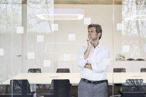 Зрелый бизнесмен смотрит на липкие заметки за стеклом в современном конференц-зале — стоковое фото