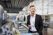 Mature businessman in factory thinking — Stock Photo
