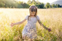 Young girl walking through field at summer evening — Stock Photo