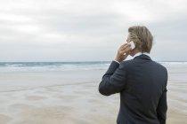 Великобритания, Корнуолл, Хейл, бизнесмен на пляже, разговаривающий по мобильному телефону — стоковое фото