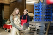 Two happy women using laptop between crates on a farm — Stock Photo