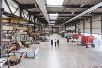 Three men walking and talking on factory shop floor — Stock Photo