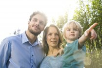 Smiling family in front of bamboo plants with son pointing his finger — Stock Photo