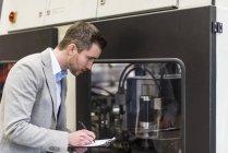 Empresário olhando para a máquina e escrevendo na área de transferência na fábrica — Fotografia de Stock