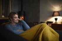Портрет улыбающейся женщины, отдыхающей дома на диване вечером — стоковое фото