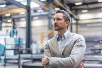 Portrait of businessman on factory shop floor thinking — Stock Photo