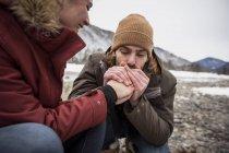 Coppia su un viaggio in inverno con uomo che scalda mani di donna — Foto stock