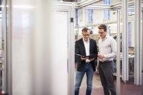 Dois empresários na fábrica olhando para a pasta — Fotografia de Stock
