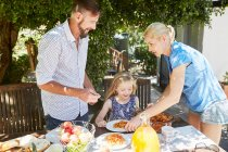 Parents dishing up pasta for daughter at garden table — Stock Photo