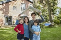 Portrait of happy family in garden of their home holding roof — Stock Photo