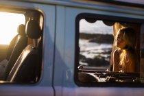 Spanien, Teneriffa, Blondes Mädchen sitzt im Van bei Sonnenuntergang — Stockfoto
