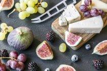 Тарелка с сыром, инжиром, виноградом, черникой, ежевиками, пеканом, разделочной доской, ножом — стоковое фото