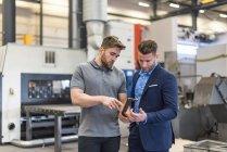 Працівник пояснивши заготовку бізнесмену на підлозі заводської майстерні — стокове фото