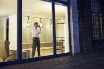 Außenansicht eines Mannes mit Smartphone in modernem Gebäude in der Nacht — Stockfoto