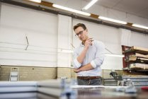 Young businessman in factory working on plan — Stock Photo