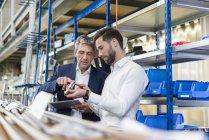 Бизнесмены во время встречи с планшетом и продуктом в производственном зале — стоковое фото