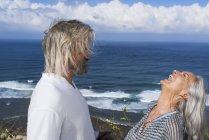 Смеющаяся старшая пара веселится на море — стоковое фото