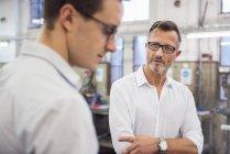 Dos hombres de negocios discutiendo en fábrica - foto de stock