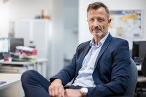 Портрет довірливого зрілого бізнесмена, який сидить за столом у офісі. — стокове фото