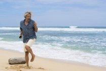 Beau senior avec écouteurs dansant sur la plage — Photo de stock