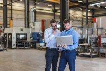 Deux hommes d'affaires partageant un ordinateur portable à l'atelier de l'usine — Photo de stock
