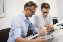 Two businessmen examining solar panel on desk in office — Stock Photo