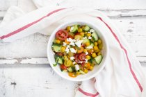 Bowl of salad with chick peas roasted with curcuma, feta, cucumber, tomatoes and parsley — стоковое фото