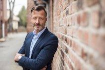 Portrait of confident mature businessman at brick wall — Stock Photo